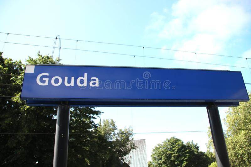 Blue name sign of Gouda on the platform of train station. royalty free stock photo