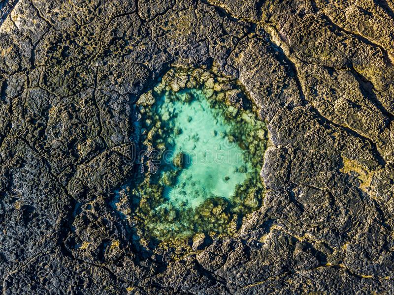 Blue natural swimming pool in the middle of black vulcanic rocks - green lagoon ocean water - aerial top view - beauty of planet stock photography