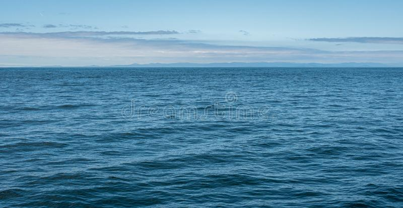Blue nature background, calm Salish Sea with blue sky, clouds, and distant land, San Juan Islands royalty free stock photo