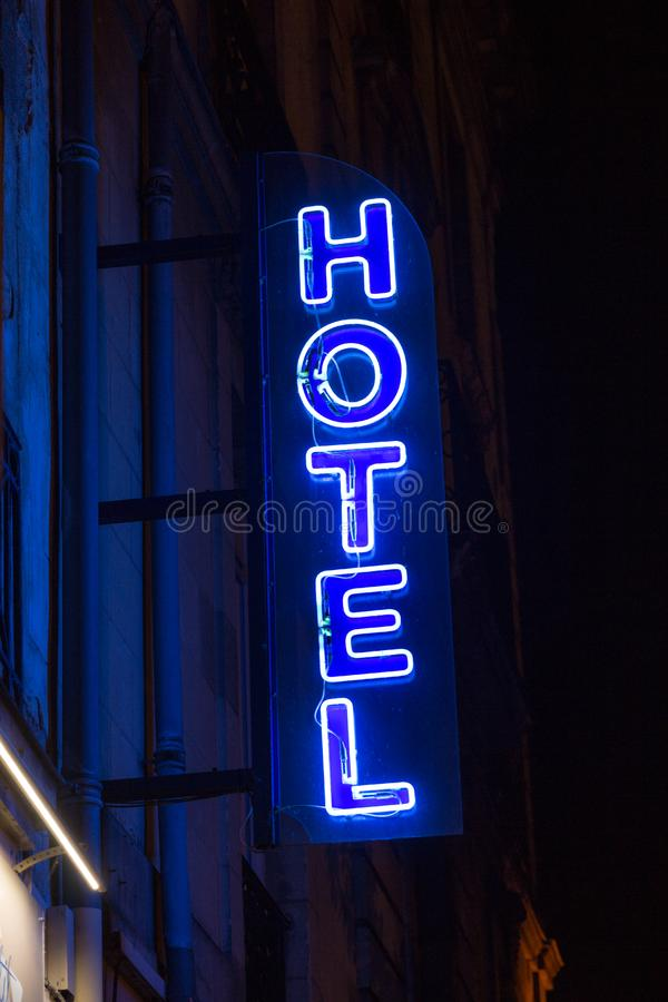 Blue neon hotel sign in the night.  stock photo