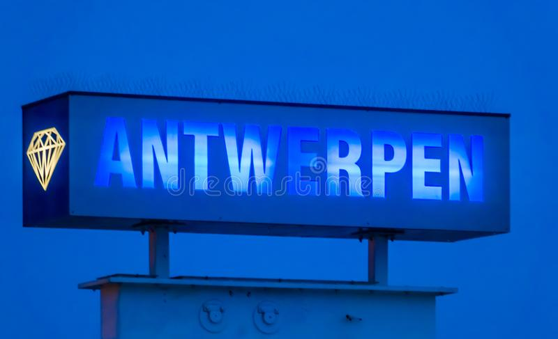 Blue neon light board with the text antwerpen, Sign post by night in antwerp, Belgium. A blue neon light board with the text antwerpen, Sign post by night in stock photo