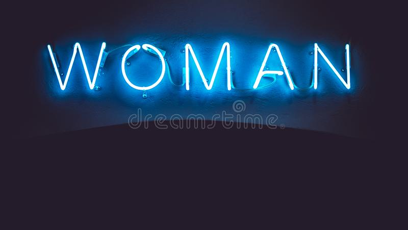 Blue neon sign of the word `Woman` on a black background.  vector illustration