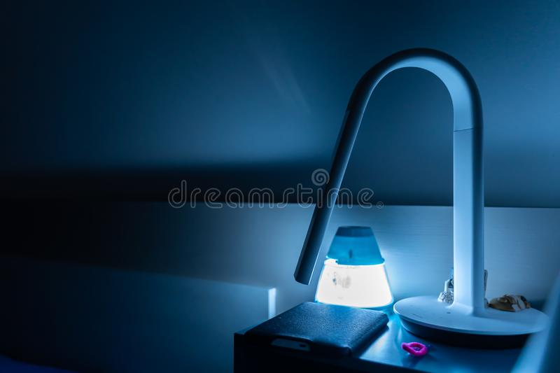Blue night from bedside table light. Blue night lamp on bedside table royalty free stock photo