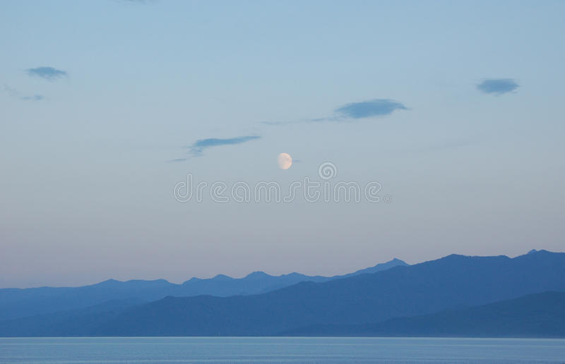 Blue night on the lake. Blue night and the moon over the low mountains on the lake stock images