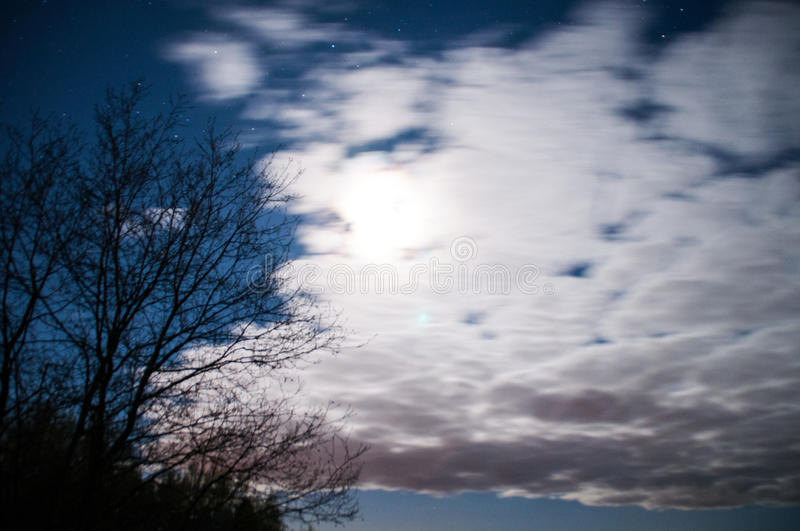 Blue night with moon under clouds royalty free stock photo