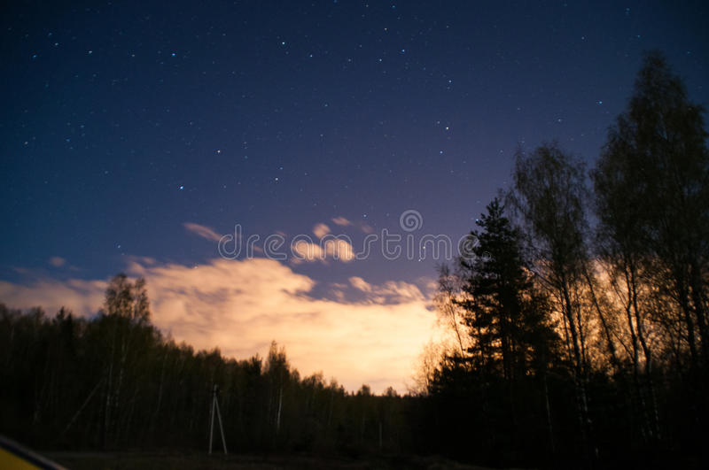 Blue night with moon under clouds royalty free stock photography