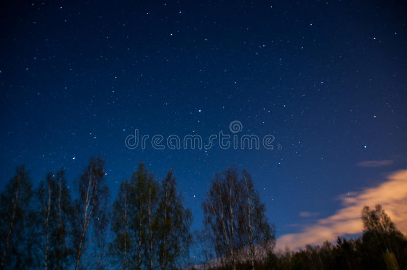 Blue night with moon under clouds stock photography