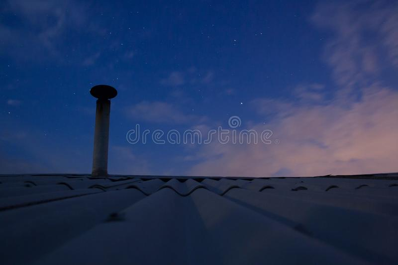 Blue night sky. On the roof with chimney stock image