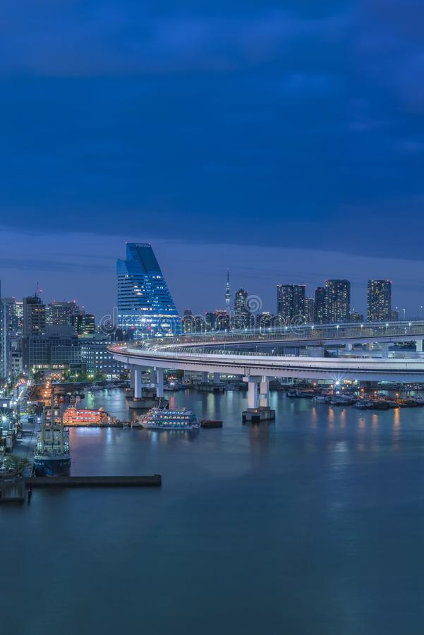 Blue night view on circular highway leading to the Rainbow Bridge with Cargo and cruise ships moored or sailing in Odaiba Bay of stock photos