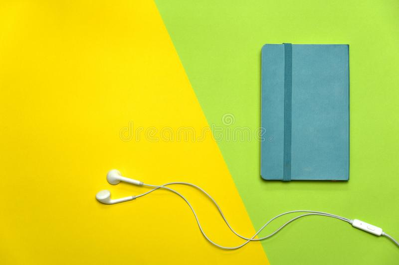 Blue note book with white earphone on green yellow education colorful background royalty free stock photography