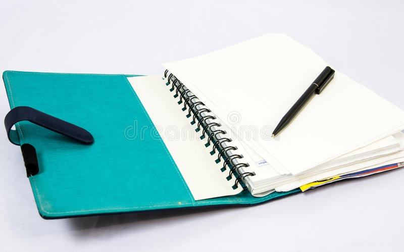 Blue notebook with pen. Isolated on white background royalty free stock photos