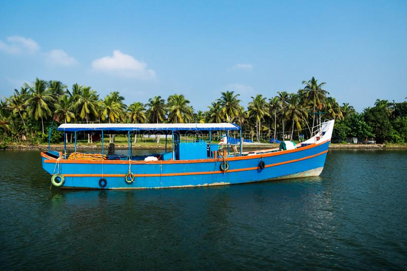Blue ocean fishing boat along the canal Kerala backwaters shore with palm trees between Alappuzha and Kollam, India 免版税库存图片