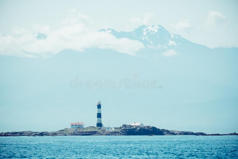 Blue Ocean Near in Black and White Lighthouse during Daytime royalty free stock photo