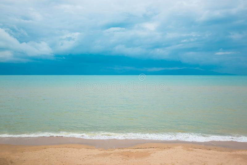Blue ocean and sand beach under cloudy sky. In a bad weather stock photos