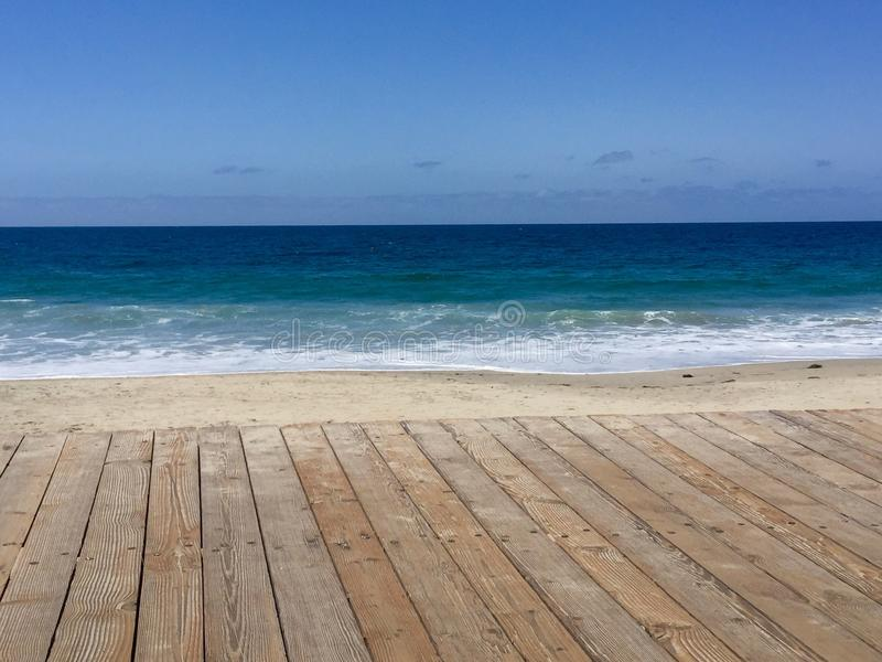 Blue ocean, sand, and Boardwalk stock photo