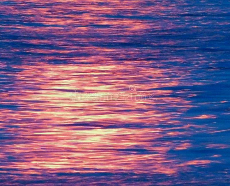 Blue ocean sea water surface in the sunset with reflections texture abstract nature horizon landscape royalty free stock photos
