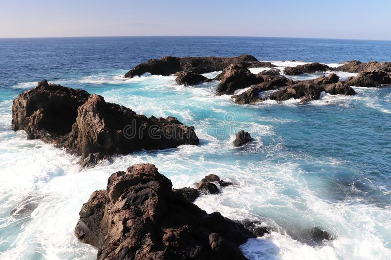 Blue ocean water crashing over rocks at a beach in Los Gigantes, Spain stock image