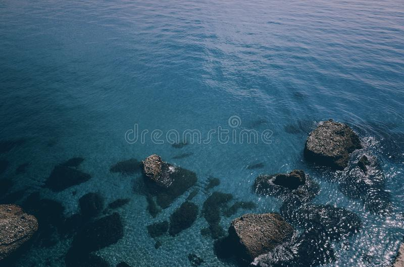 Blue ocean water with stones stock photos