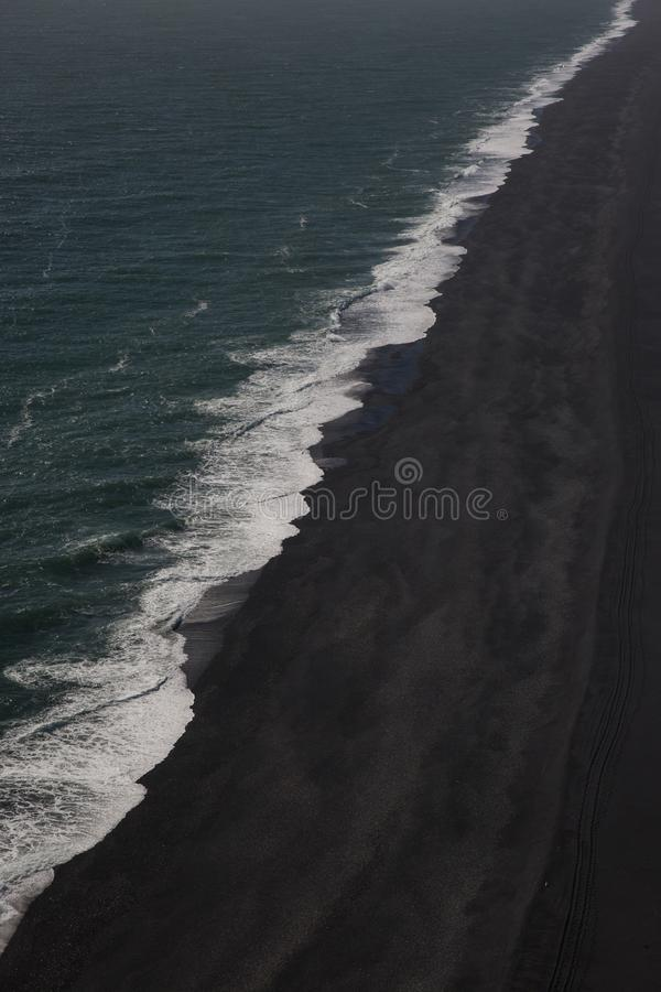 Aerial view of Iceland ocean wave cresting on black sand beach stock images