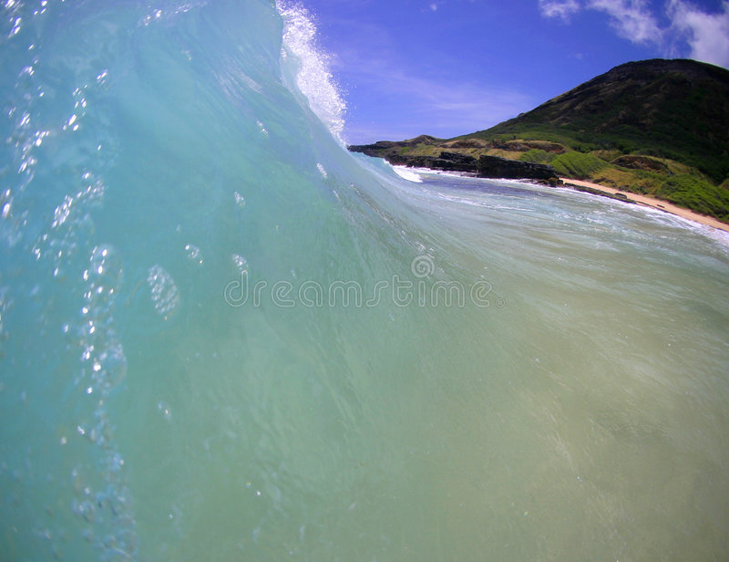 Blue Ocean Wave at the Beach in Hawaii. Stock Photo of a Wave Surging towards the shore in Hawaii royalty free stock image