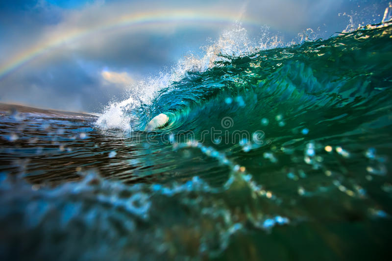 Blue Ocean Wave with Rainbow is a symbol of Hawaii. Ocean Background Big Shorebreak Wave for Surfing. Hawaiian swell for sport activity. Power and Energy Of royalty free stock photography