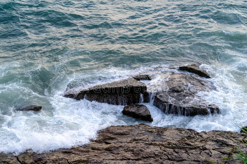The blue ocean waves hit the big rock, top view stock images