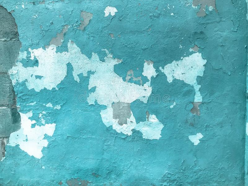 The blue old shabby cracked wall is ancient beautiful with peeling paint. Texture. The background royalty free stock images