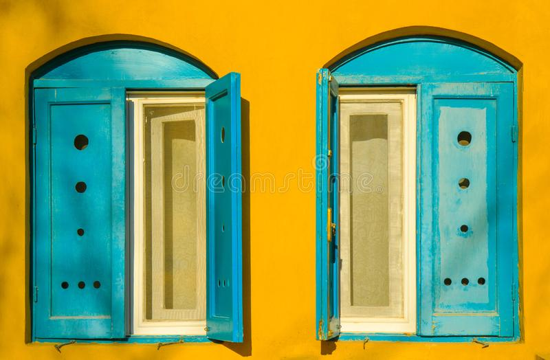Blue old style wooden windows, symmetry in open doors, yellow house wall background in small town, minimal style of simplicity, royalty free stock images