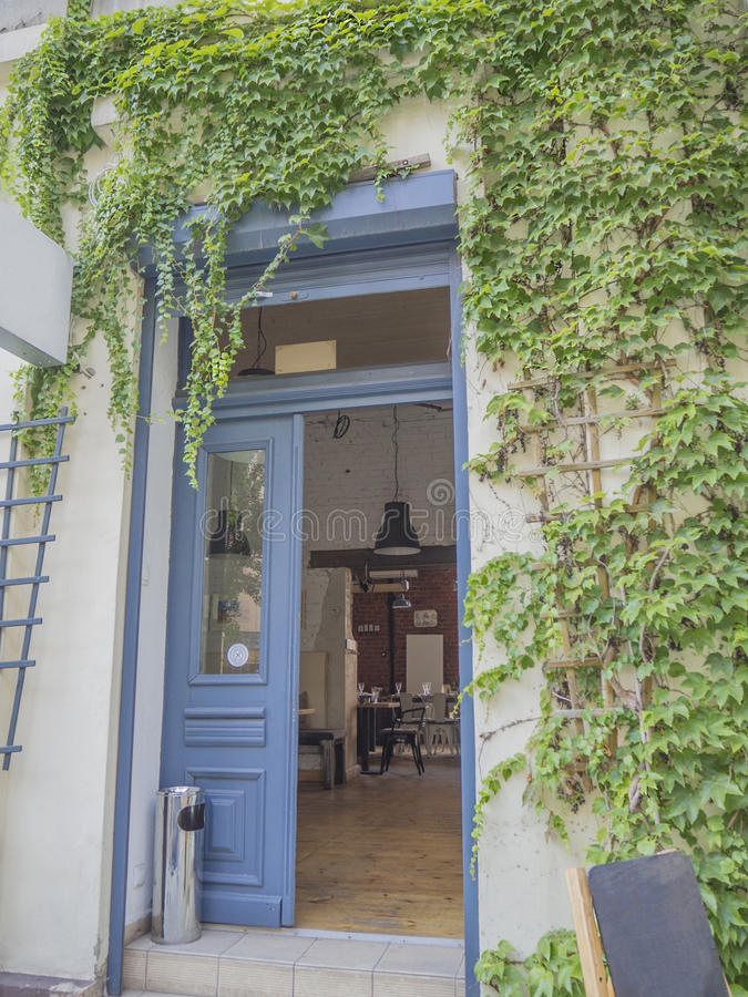 blue open door ivy covered with view on vintage industrial cofee bar royalty free stock photos