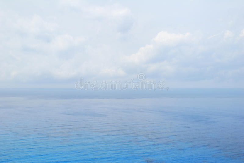 Blue open sea water and sky. Blue open sea water under cloudy sky stock images