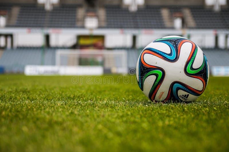 Blue Orange Black Green White Adidas Soccer Ball on Green Field stock photo