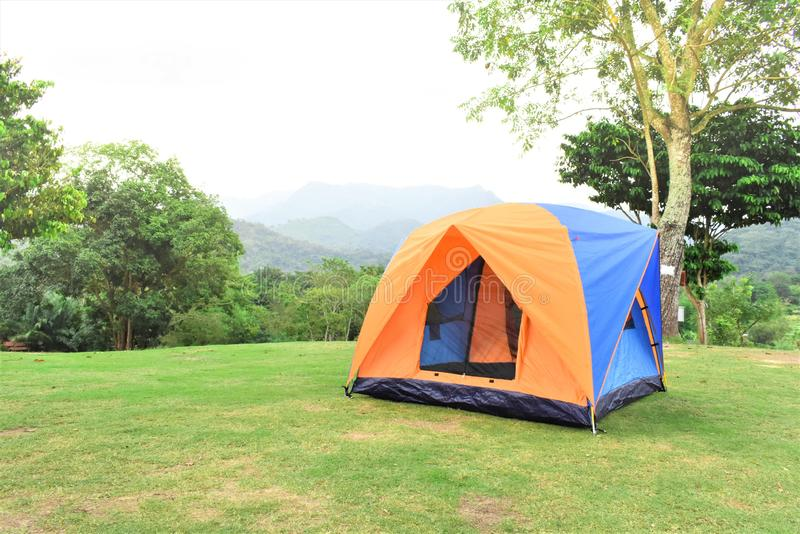 Orange color family camping tent with ground sheet setup on green park campsite. Blue and Orange color family camping tent with ground sheet setup on green park stock images