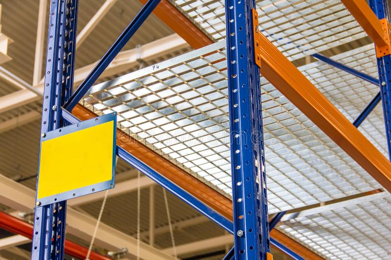 Blue and orange metal shelves for storing goods. In a large warehouse complex, close-up, labeling plate stock photos