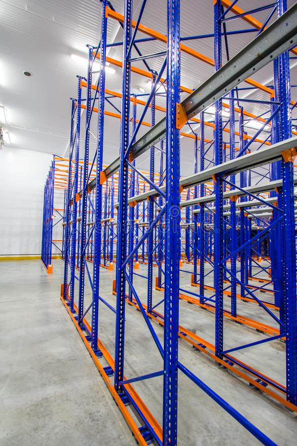 Blue and orange metal shelves for storing goods in a large warehouse complex. Huge areas for storage of goods, storage rack, blue and orange metal shelves for stock image