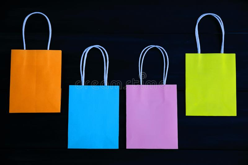 Blue, orange, pink and yellow gift bags on a dark wooden background, semicircle stock photos