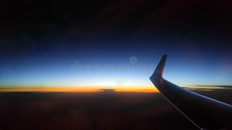 Blue orange sunset from a sky height. Airplane wing royalty free stock photo