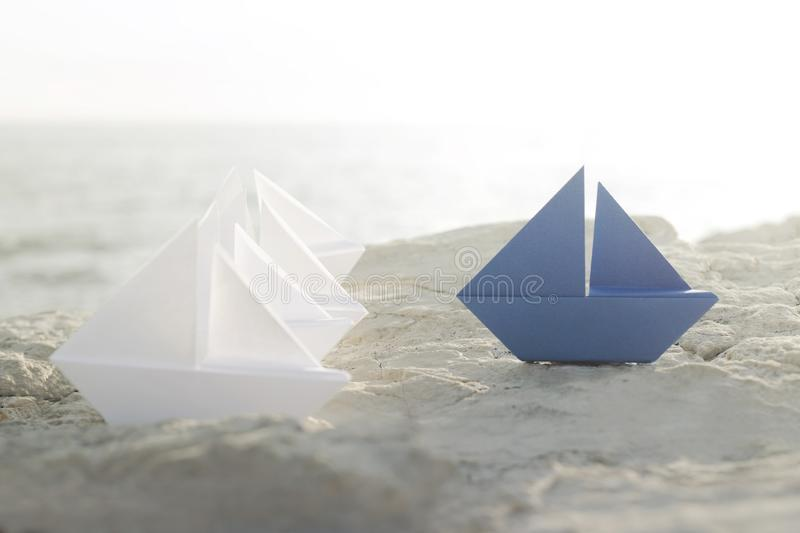 Blue origami boat stands on white ship, concept of difference, success, leadership royalty free stock images