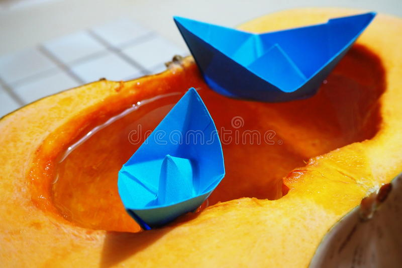 Blue origami paper boat sailing on water in orange pumpkin stock photo