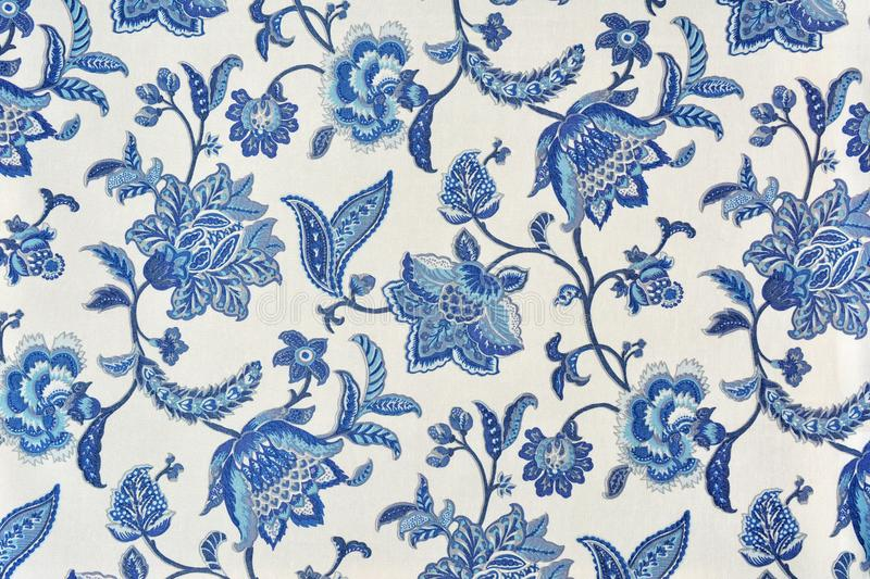 Blue ornate floral pattern on white cotton tablecloth. royalty free stock photography
