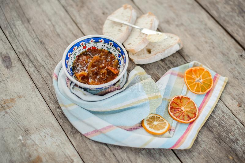 Blue ornate plate with a delicious orange jam on the napkin with dried oranges near the bread with butter royalty free stock photography