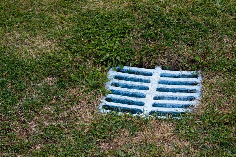 Blue water drain. Blue outdoor old square water drain in grass stock images