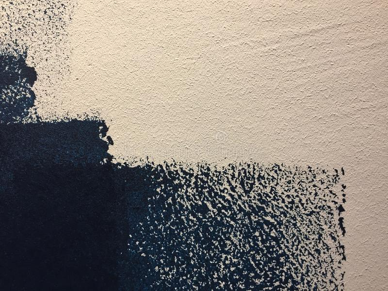 Blue paint patterns in freshly painted white wall with single brush strokes visible. Unfinished job royalty free stock image