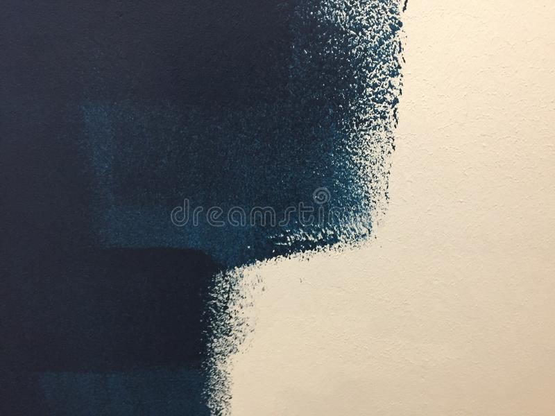 Blue paint patterns in freshly painted white wall with single brush strokes visible. Unfinished job stock images