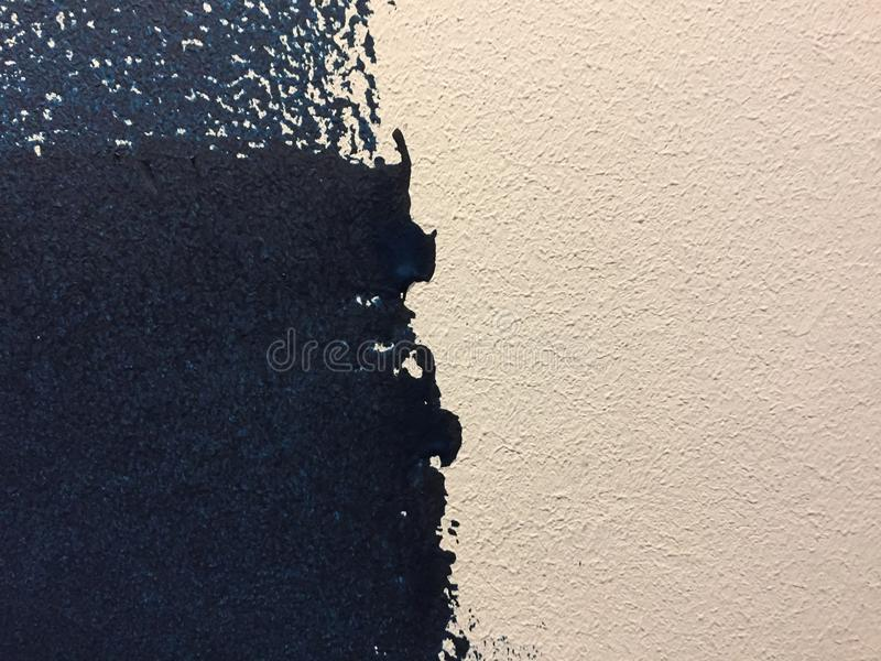 Blue paint patterns in freshly painted white wall with single brush strokes visible. Unfinished job stock photography
