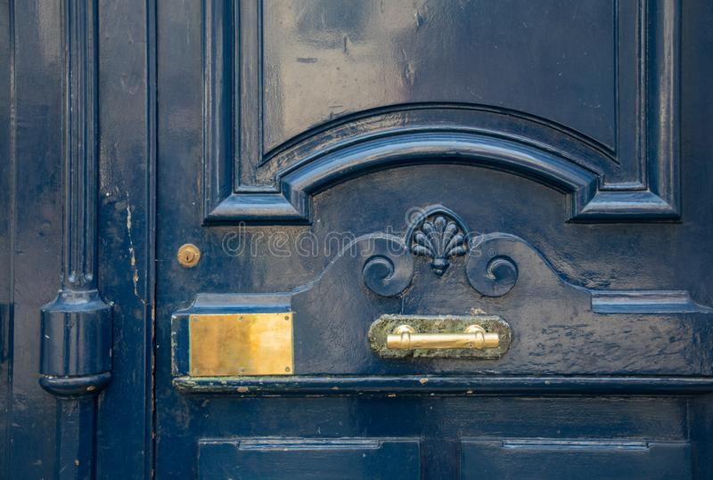 Blue painted antique door closeup with curved frame and elegant volute carving wooden panel with shiny brass plate and door handle. Vintage door details royalty free stock photo