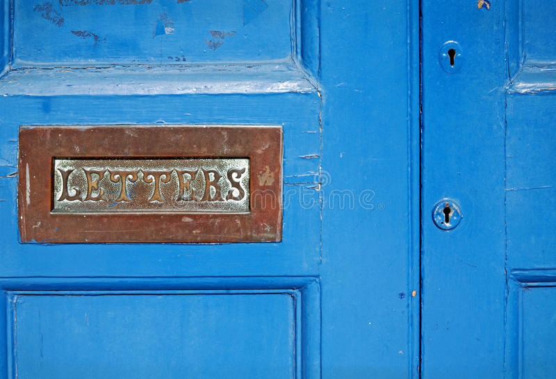 Blue painted door with brass letterbox royalty free stock photography
