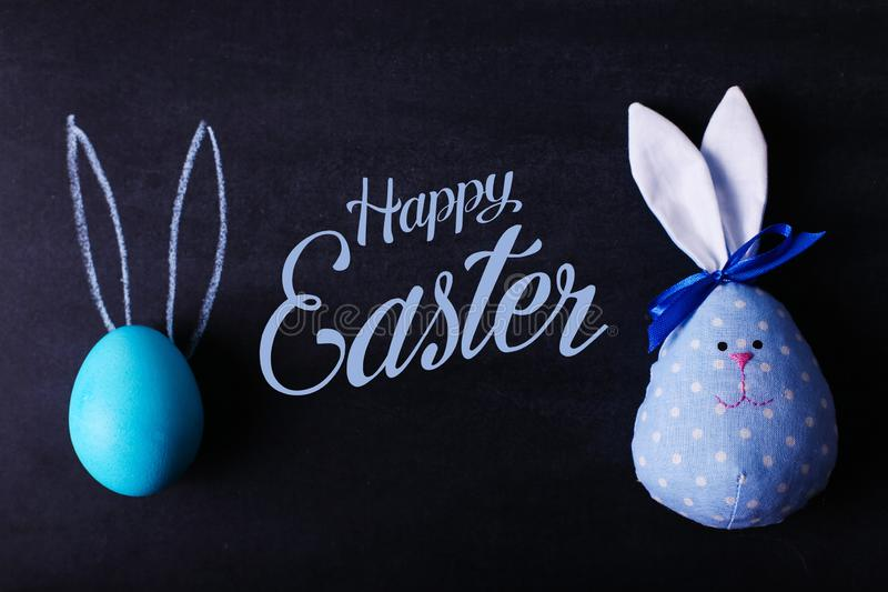 A blue painted Easter egg on a chalkboard with pressed ears looks like a rabbit. And the hare is handmade from fabric. Text, happy royalty free stock images