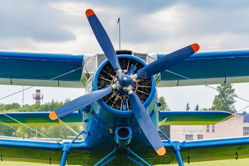 Blue painted legendary soviet aircraft biplane Antonov AN-2 closeup parked on the airfield against cloudy sky stock image