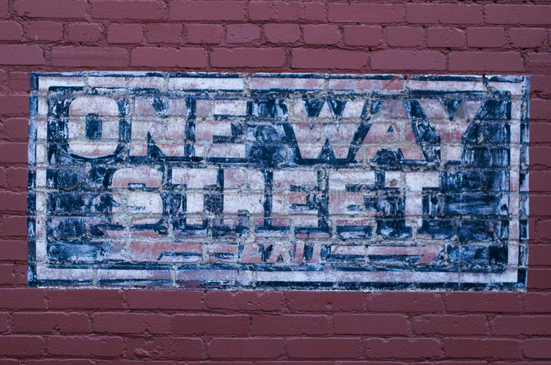 Blue painted one way traffic street sign. Blue and white One way street sign painted on red brick wall royalty free stock photo