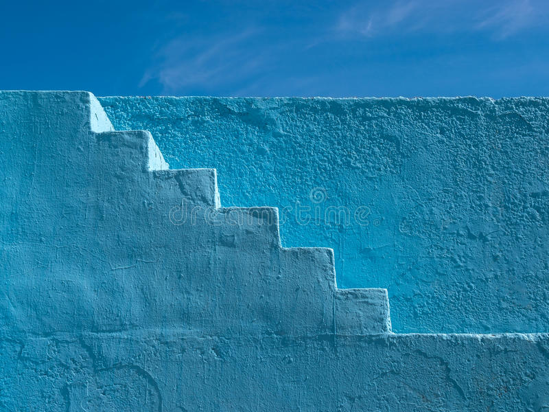 Blue Painted Steps Pattern. Abstract pattern of blue painted steps going up the side of a wall, against a deep blue sky stock photography